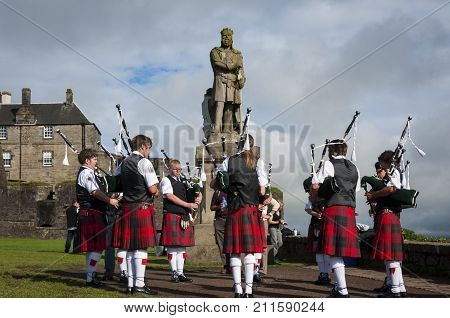 Stirling Scotland - August 17 2010: Band of pipers playing in front of the statue of Robert the Bruce in the Stirling Castle in Stirling Scotland United Kingdom