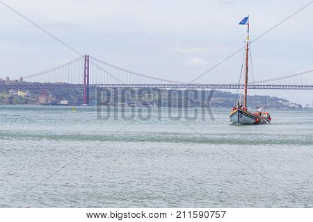Sailboat and bridge in Tejo River Lisboa Portugal