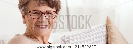 Happy senior lady sitting on the couch in retirement home