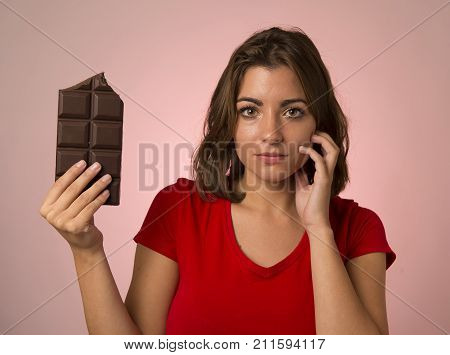 young beautiful happy and excited woman holding big chocolate bar in sugar addiction temptation looking guilty skipping diet in unhealthy nutrition lifestyle and overweight concept