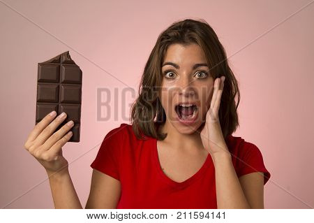 young beautiful happy and excited woman holding big chocolate bar screaming in sugar addiction temptation looking crazy skipping diet in unhealthy nutrition lifestyle and overweight concept