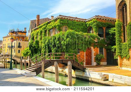 Houses Covered With Ivy Along Narrow Canal With Bridges In Venice, Italy.