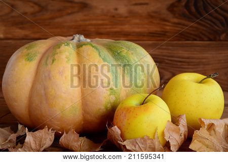 Fresh pumpkin and apples on a wooden background. Dry autumn leaves. Fall harvest. Healthy diet food. Closeup