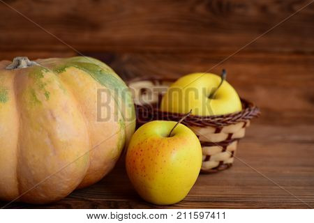 Sweet pumpkin and apples on a wooden background. Autumn harvest. Healthy diet. Closeup
