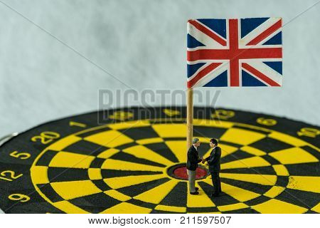 Brexit negotiation agreement concept as miniature people: Small figure businessmen handshaking and standing at the center of dartboard with the United Kingdom flag.