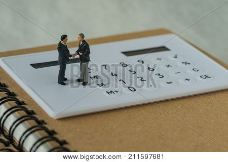 Miniature people: Small figure businessmen handshaking and standing on white calculator and notebook as business agreement concept.
