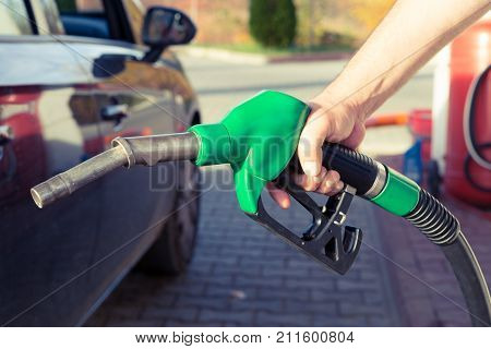 Man hand holding gasoline pump in a gas station ready to fill the tank or to refuel as expensive fuel concept with price rising