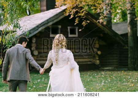 Bride and groom go to wooden home in the forest. Young newlyweds walking in the park. Autumn wedding. Artwork