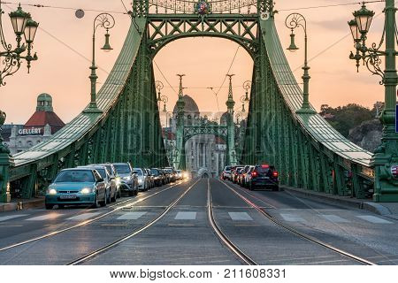 BUDAPEST HUNGARY - SEPTEMBER 27, 2017: Traffic on Liberty bridge. Evening traffic on the iconic Liberty bridge with the Gellért building in the background in Budapest Hungary on September 27, 2017.