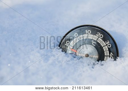 Vintage thermometer with celsius scale showing sub-zero temperature placed in a fresh snow in winter
