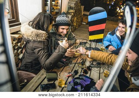 Happy friends drinking beer and eating chips at apres ski - Friendship concept with cheerful people having fun at bar restaurant resort with snow equipment - High iso image with shallow depth of field