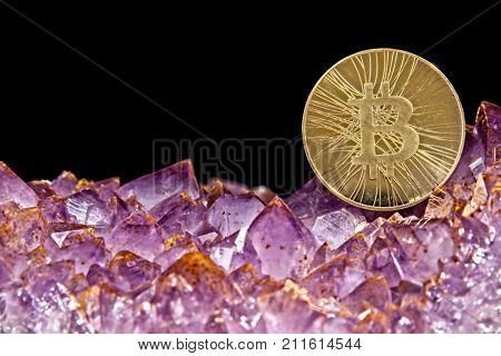 Bitcoin coin on pink Amethyst gemstone crystal geode on black background.