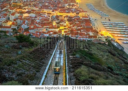 Nazare, Portugal by evening, the most popular seaside resorts in Silver Coast. Prospective view of popular Ascensor da Nazare or Nazare Funicular from Nazare Sitio, the upper part of city.