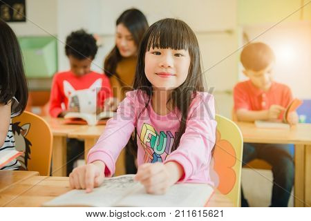 Asian girl reading a book smiling at the camera. Row of multiethnic elementary students reading book in classroom at school. Vintage effect style pictures.