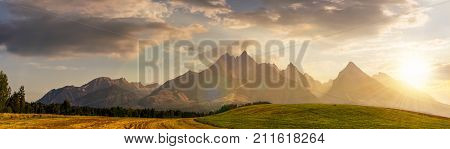 rural fields near Tatra Mountains in summer at sunset. beautiful panorama of agricultural area. gorgeous mountain ridge with high rocky peaks