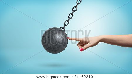 A giant female arm with one finger lightly touching a black iron wrecking ball and stopping its movement. Business and risks. Corporate consultant. Helpful accounting.