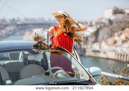 Young woman in red dress traveling by car in Porto city, Portugal