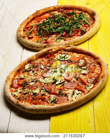 Pizza With Pepperoni, Mushrooms And Egg On Yellow Wooden Background