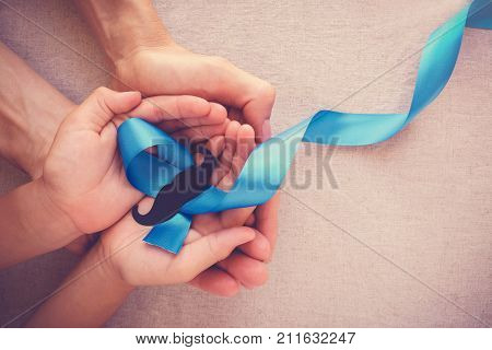 Adult and child hands holding Light blue ribbons with mustache Prostate Cancer Awareness Men health awareness Movember month