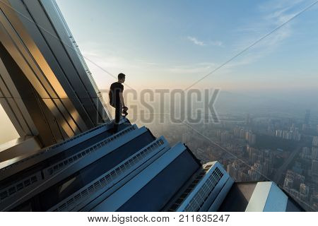 SHENZHEN, CHINA - AUG 26, 2015: Man (with MR) on rooftop in morning, Ping An Finance Centre