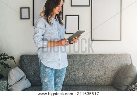 Young woman with blond hair is standing in living room next to sofa and uses tablet computer, blogging, chatting.Freelancer works at home.Social media, network.Online marketing, education, e-learning.