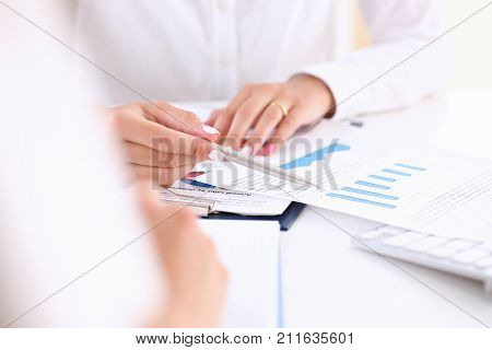 Businesswoman holding a silvery pen in her hand indicates the interlocutor for a digram on the form of annual report on the financing of organizations trains the processing of this statistical study. poster