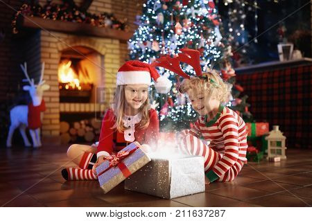 Child At Christmas Tree. Kids At Fireplace On Xmas