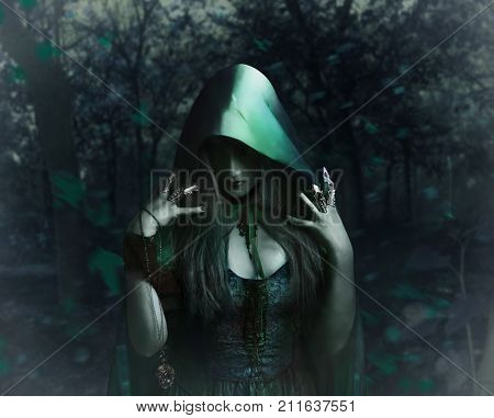 Beautiful sorceress in green cloak holding antique watch standing in the night forest photo.