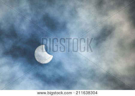 oon over sun in eclipse on blue cloudy background