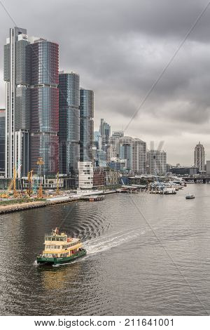 Sydney Australia - March 21 2017: HSBC Office towers on shore of Darling Harbour with more towers in back under heavy gray skyline. Ferry approaches on the water. More towers in back.
