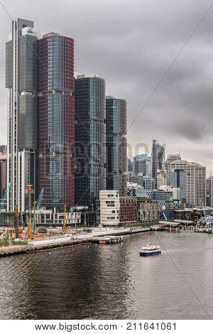 Sydney Australia - March 21 2017: HSBC Office towers on shore of Darling Harbour under heavy gray skyline. Ferry approaches on the water. Construction cranes in front.