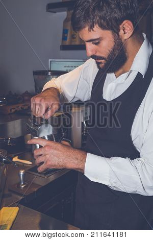 Barista making cappuccino in his coffeeshop or cafe