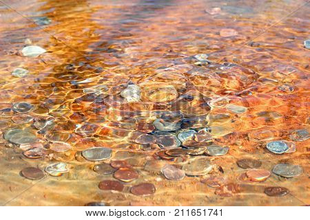 coins laying on the bottom of water fountain