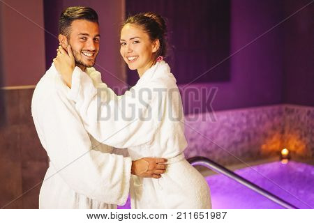 Happy young couple wearing bathrobe enjoying the spa day during their honeymoon - Romantic lovers having relax in a hotel spa ready to do a bathtub jacuzzi - Concept about people and well being
