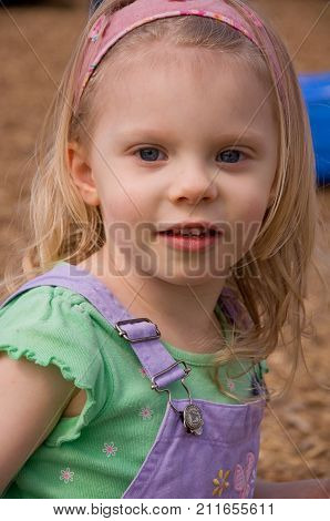 This is a vertical image of a cute 4 year old Caucasian girl's portrait outsides.