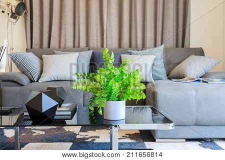 Artificial tree in white pot on sofa table with many pillows in living room.