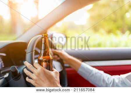 Drunk young man drives a car with a bottle of beer with sunset background Dangerous driving concept