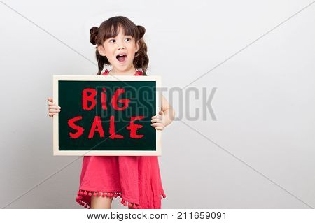 big sale discount for item in shopping mall promotion on end of year concept : adorable girl act surprise face holding chalk sign board with text big sale in red. copy space for your text