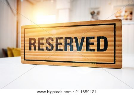 Reservation seat at restaurant for dating on celebrate day concept. Restaurant with reserved wooden sign on white table with cafe decorate places setting and evening light with bokeh for dinner time