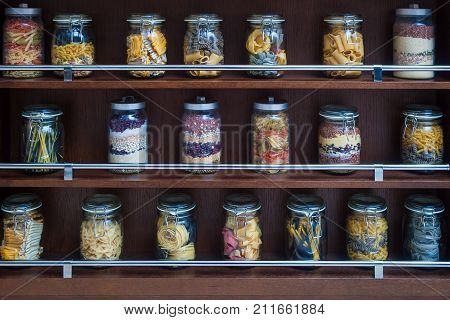 On the wooden shelves are glass jars with various varicoloured types of pasta spaghetti beans cereals for their storage and decorating the kitchen