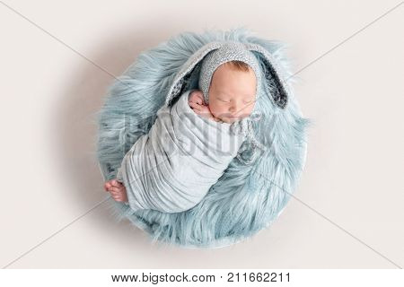 Newborn baby in funny hat sleeping on fluffy blanket, top view.