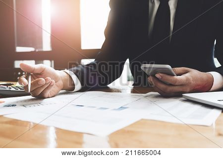 Businessman Pen Pointing Graph Chart In This Mounth And Use Smart Phone For Calculating Market Plan,