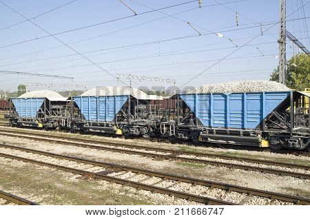 Three freight wagons with gravel on the siding on station
