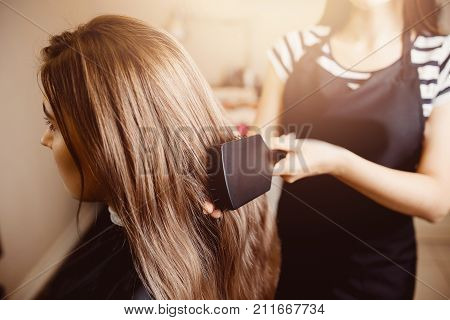 Comb hair. The master in the hairdresser prepares the client's girl to restore the procedures