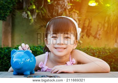 Happy asian girl with big smile put her coin in the blue piggy bank selective focus for business or education concept.
