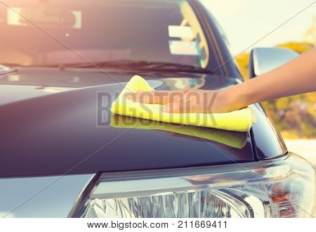 Girl's hand wiping on surface of car shine.