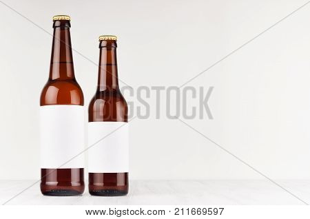 Brown beer bottles longneck 500ml and 330ml with blank white label on white wooden board mock up. Template for advertising design branding identity.