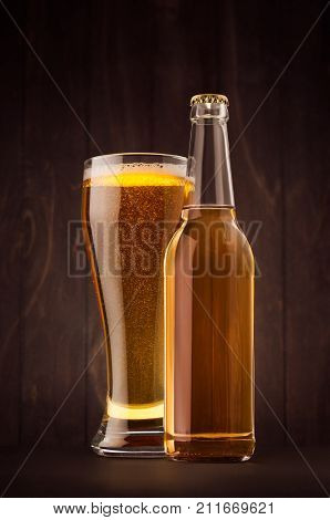 Transparent beer bottle and glass weizen with golden lager on dark brown wood board vertical mock up. Template for advertising design branding identity.