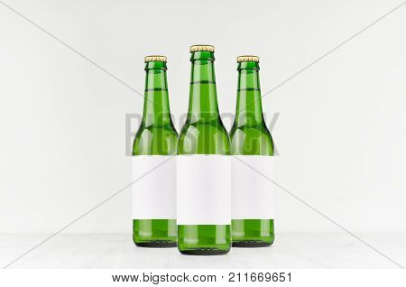 Three green longneck beer bottles 330ml with blank white label on white wooden board mock up. Template for advertising design branding identity.