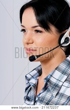Close up portrait of smiling female helpline operator with headphones giving a consultation